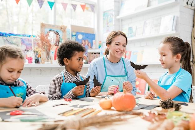 Groep eigentijdse ijverige schoolkinderen die halloween-speelgoed maken en aan gelukkige leraar tonen