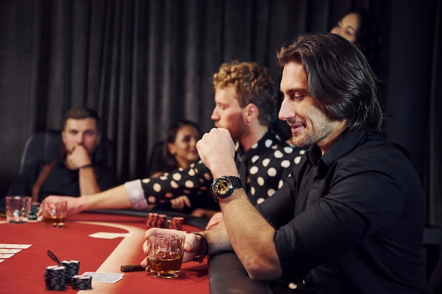 Groep elegante jongeren die samen pokeren in casino