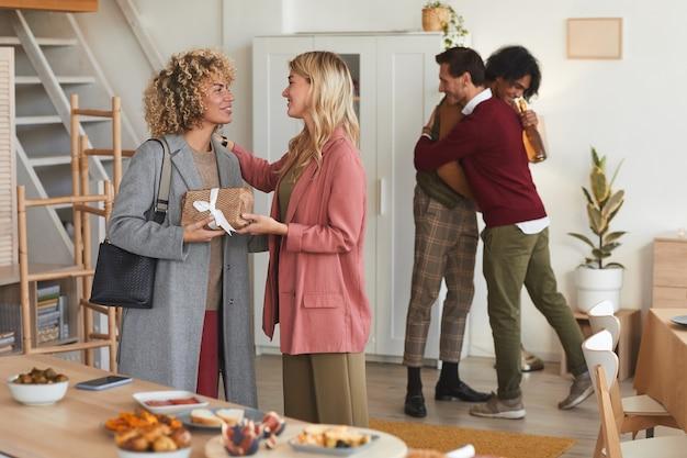 Groep elegante volwassen mensen die elkaar begroeten en geschenken uitwisselen terwijl ze gasten verwelkomen op een etentje binnenshuis