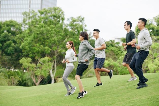 Groep en jonge vietnamese sporters die de heuvel af rennen tijdens het trainen in het stadspark