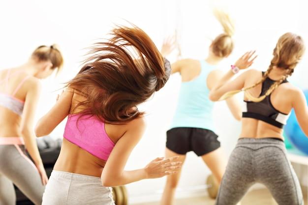 Groep energieke mensen met coach dansen in sportschool