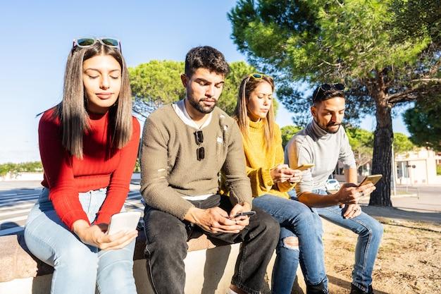 Groep ernstige jonge mensen die op een stadsmuur zitten die tijd doorbrengen met behulp van smartphone met mobiele verbinding.