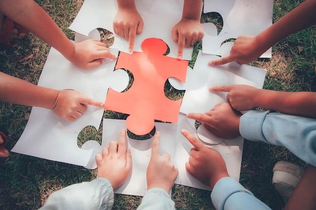 Groep etnisch diverse kinderen studenten wordt samengevoegd spelen puzzel / puzzels stukken samen in de speeltuin. teamwork, samenwerking, leren en onderwijsconcept.