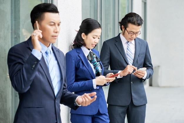 Groep etnische bedrijfsmensen die hun telefoons in openlucht met behulp van