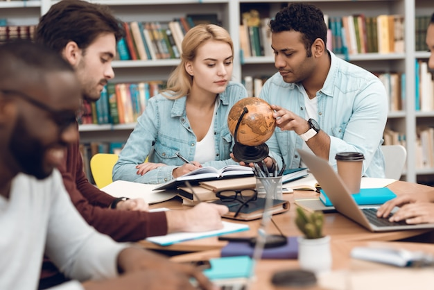 Groep etnische multiculturele studenten die aan tafel zitten.