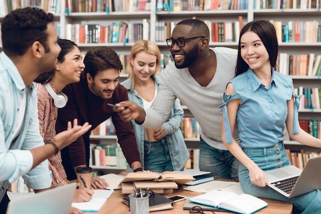 Groep etnische multiculturele studenten die het bestuderen bespreken.