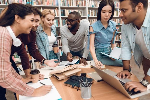 Groep etnische multiculturele studenten die in bibliotheek bespreken