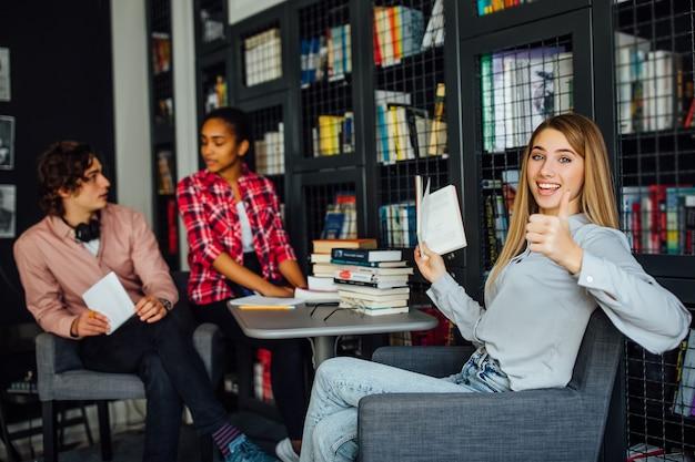 Groep etnische multiculturele studenten zitten aan tafel in bibliotheek