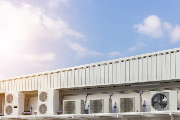 Groep externe airconditioning en compressoreneenheden buiten een gebouw met blauwe hemelachtergrond