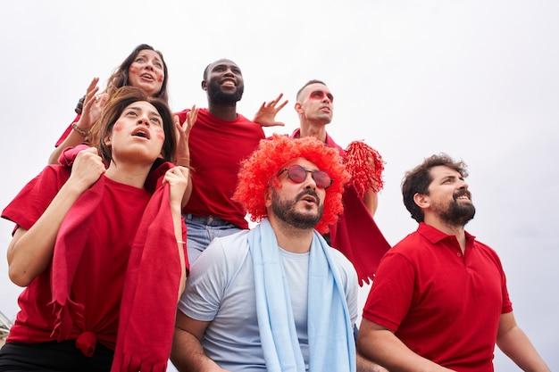 Groep fans van een voetbalteam op de tribunes die rode shirts dragen met een fan van het andere team