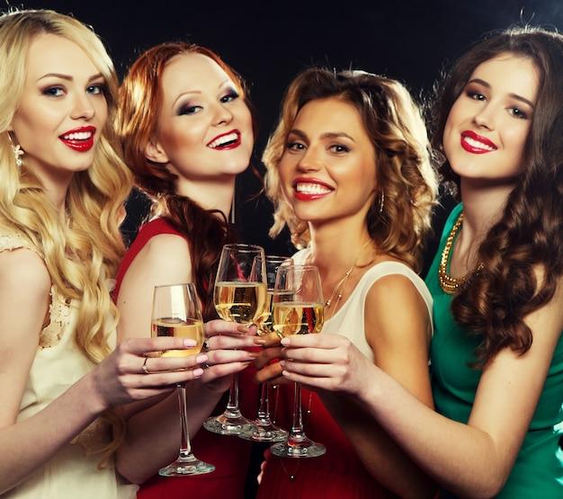 Groep feestende meisjes die op fluiten klinken met mousserende wijn