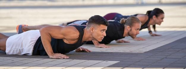 Groep fitnessmensen die push-ups doen in de stad