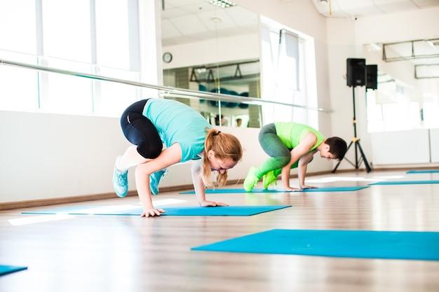 Groep fitnessvrouwen traint op de matten in de sportschool