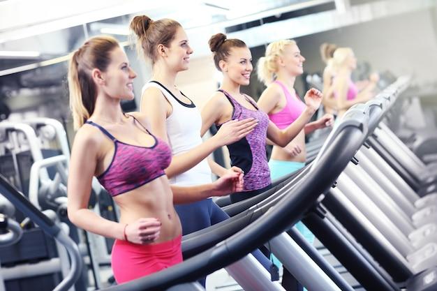 Groep fitte vrouwen die trainen op de loopband in de sportschool