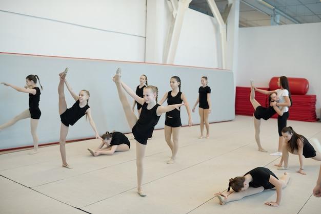 Groep flexibele tienermeisjes die split- of warming-up rekoefeningen doen bij cheerleading training