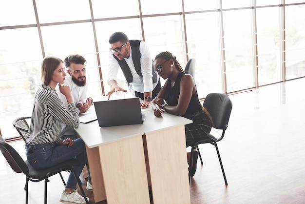 Groep freelancers die in het ruime kantoor met grote ramen werken
