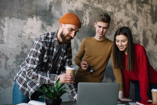 Groep freelancers die samen gebruikend laptop in bureau samenwerken