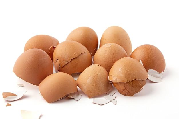 Groep gebroken eierschalen geïsoleerd op een witte achtergrond. eierschalen zijn ovaal, bruin, broos en dun, gemakkelijk te breken.
