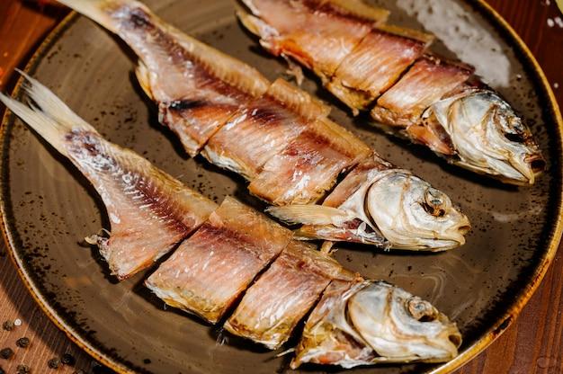 Groep gedroogde vis op plaat. zeevruchten