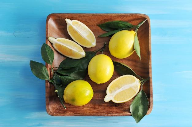 Groep gele citroenen met bladeren op een vierkante houten plaat op blauwe houten achtergrond
