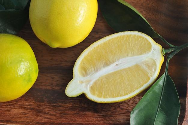 Groep gele citroenen met bladeren op houten plaat