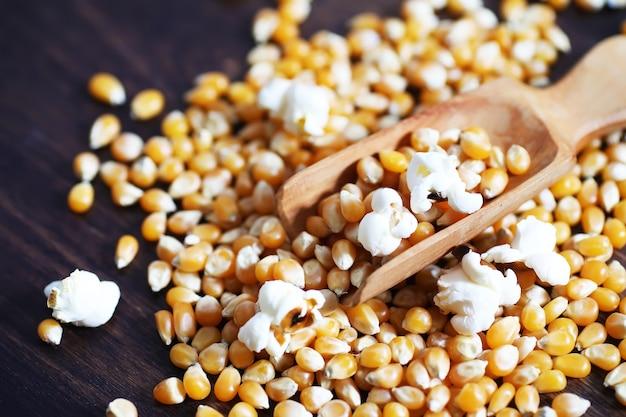 Groep gele rauwe maïskorrels suikermaïs. graanzaden ingrediënt gouden maïskorrel. houten tafel rijpe popcorn achtergrond.