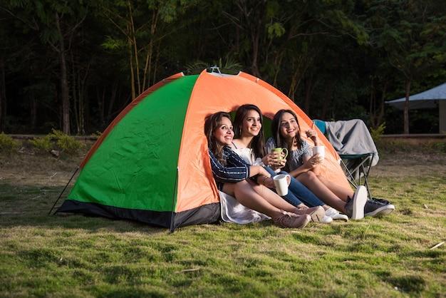 Groep gelukkige aziatische indiase mooie meisjes die bij de tent kamperen. outdoor-activiteit, avontuurlijke reizen of vakantievakantieconcept
