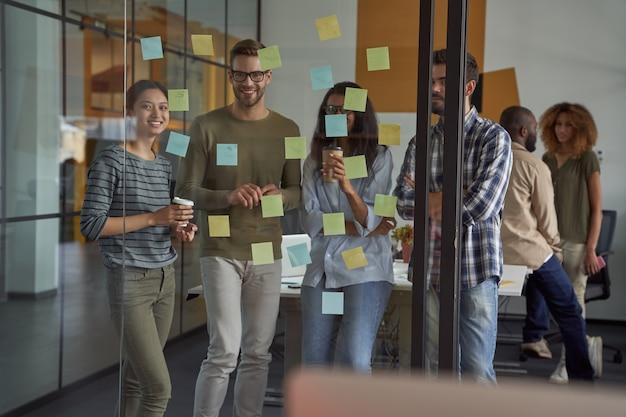 Groep gelukkige creatieve mensen of collega's die naar plaknotities op een glazen bord kijken en glimlachen