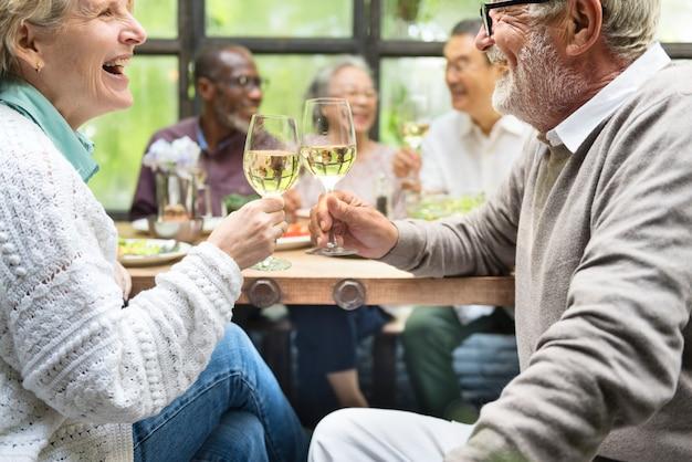 Groep gelukkige gepensioneerde senioren ontmoeten in een restaurant