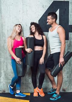 Groep gelukkige geschikte mensen die op muur in gymnastiek leunen