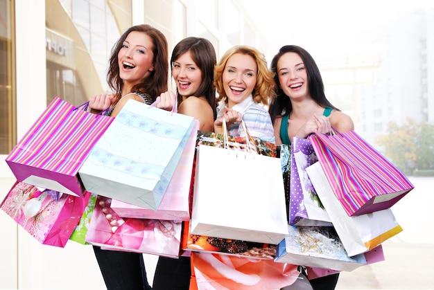 Groep gelukkige glimlachende vrouwen die met gekleurde zakken winkelen