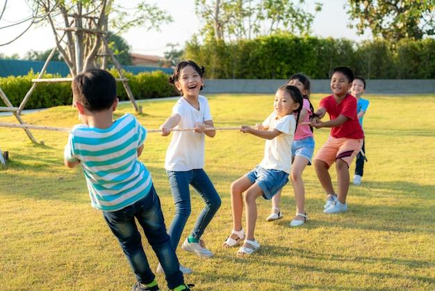 Groep gelukkige jonge aziatische kinderen die touwtrekwedstrijd spelen of touw samen in de stadsparkspeelplaats trekken in de zomerdag. kinderen en recreatie concept.