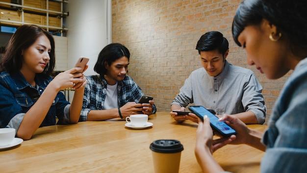 Groep gelukkige jonge azië-vrienden die plezier hebben en samen smartphone gebruiken terwijl ze samen in café-restaurant zitten.