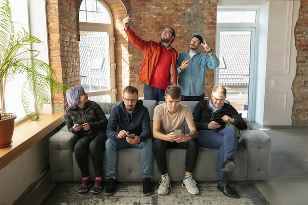Groep gelukkige jonge blanke mensen die samen op een bank zitten.