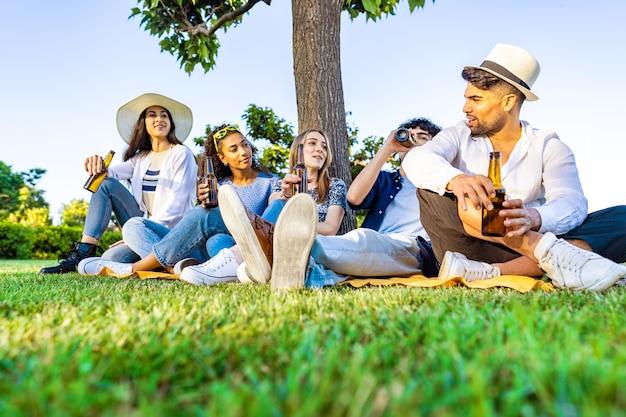 Groep gelukkige jonge diverse multiraciale gen z-mensen in een buitenfeest die bier uit de fles drinkt