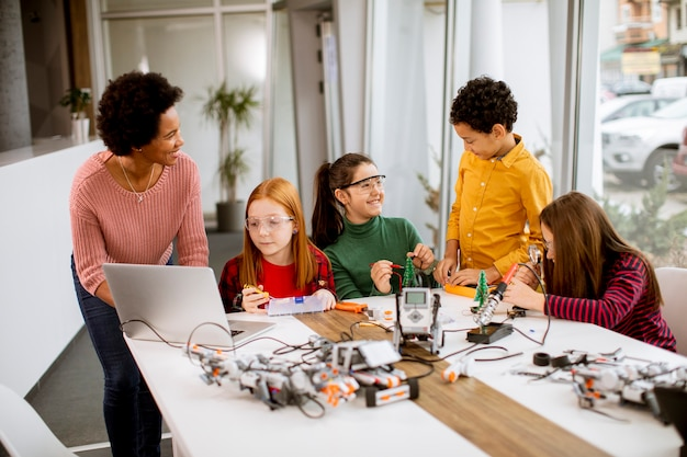 Groep gelukkige jonge geitjes met hun afrikaanse amerikaanse vrouwelijke wetenschapsleraar met laptop die elektrisch speelgoed en robots programmeren bij robotica-klas