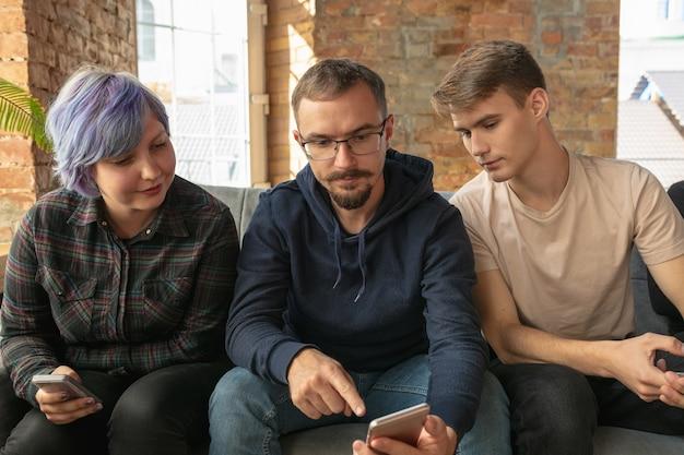 Groep gelukkige jonge mensen die op sociale media delen
