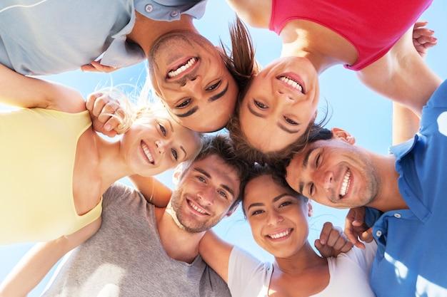 Groep gelukkige jonge mensen in cirkel buitenshuis