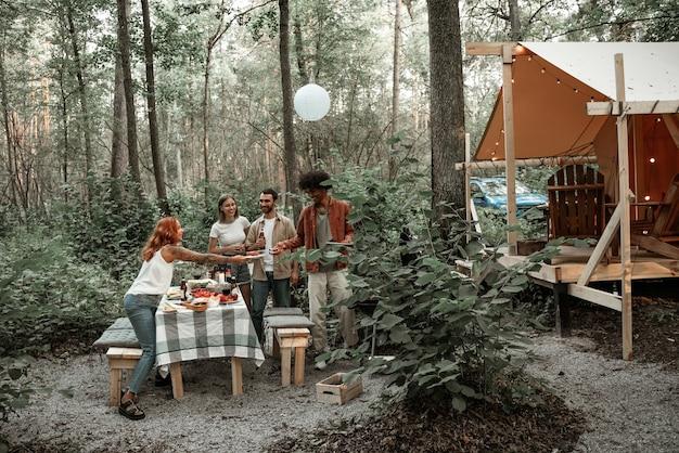 Groep gelukkige jonge vrienden die barbecue maken in het bos in glamping. afrikaanse man die worstjes grilt en kampvoedsel doorgeeft aan zijn vriend, lachen, plezier hebben op een picknick op het platteland, grillen
