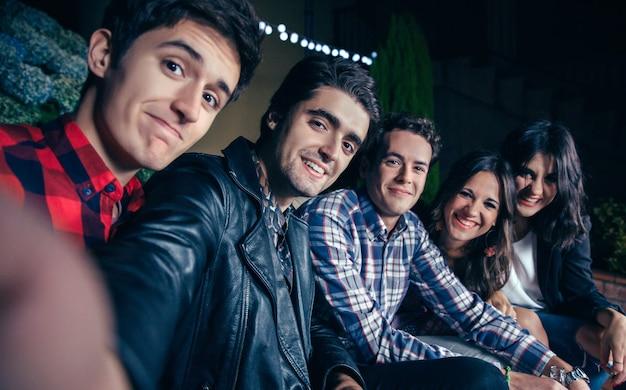 Groep gelukkige jonge vrienden die glimlachen terwijl ze een selfie-foto maken op een buitenfeest. vriendschap en vieringen concept.