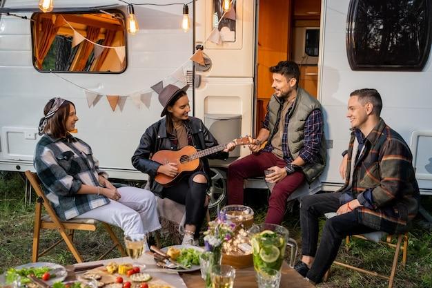 Groep gelukkige jonge vrienden die liedjes zingen per huis op wielen