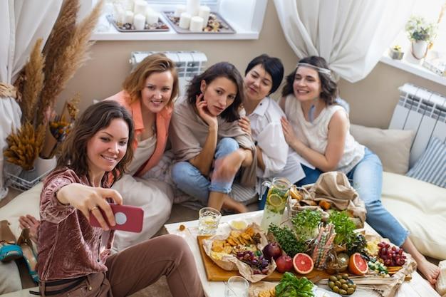 Groep gelukkige jonge vriendinnen poseren nemen selfie smartphone gebruiken op henparty in hippiestijl