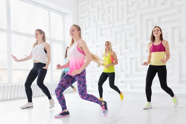 Groep gelukkige jonge vrouwen die een fitness-dansles hebben in de witte dansstudio met raam op de achtergrond