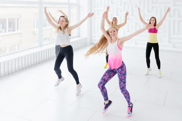 Groep gelukkige jonge vrouwen die een fitness-dansles hebben