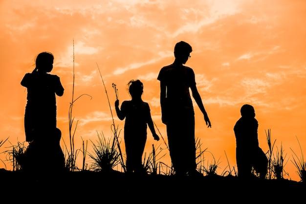 Groep gelukkige kinderen die bij zonsondergang op weide spelen