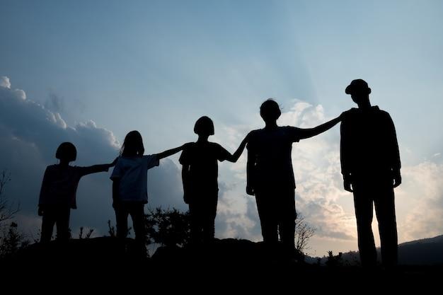 Groep gelukkige kinderen die bij zonsondergang, silhouet spelen