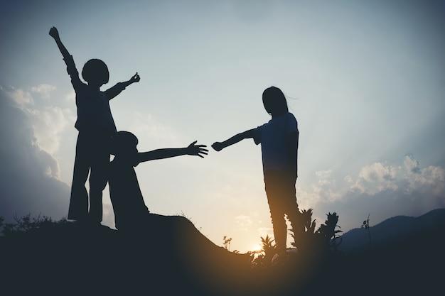 Groep gelukkige kinderen die op de berg bij zonsondergang, silhouet spelen