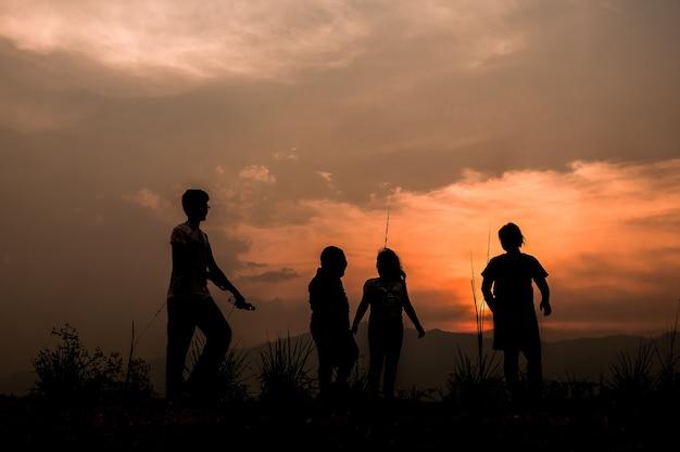Groep gelukkige kinderen die op weide bij zonsondergang spelen