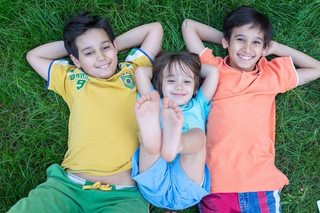 Groep gelukkige kinderen in de zomer die op groen gras liggen