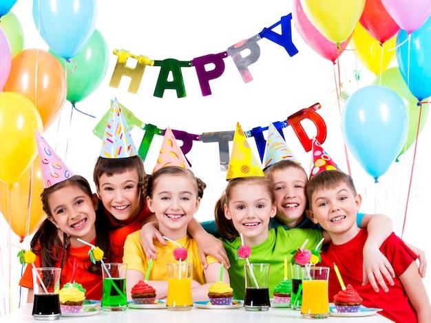 Groep gelukkige kinderen in kleurrijke shirts met plezier op het verjaardagsfeestje - geïsoleerd op een witte
